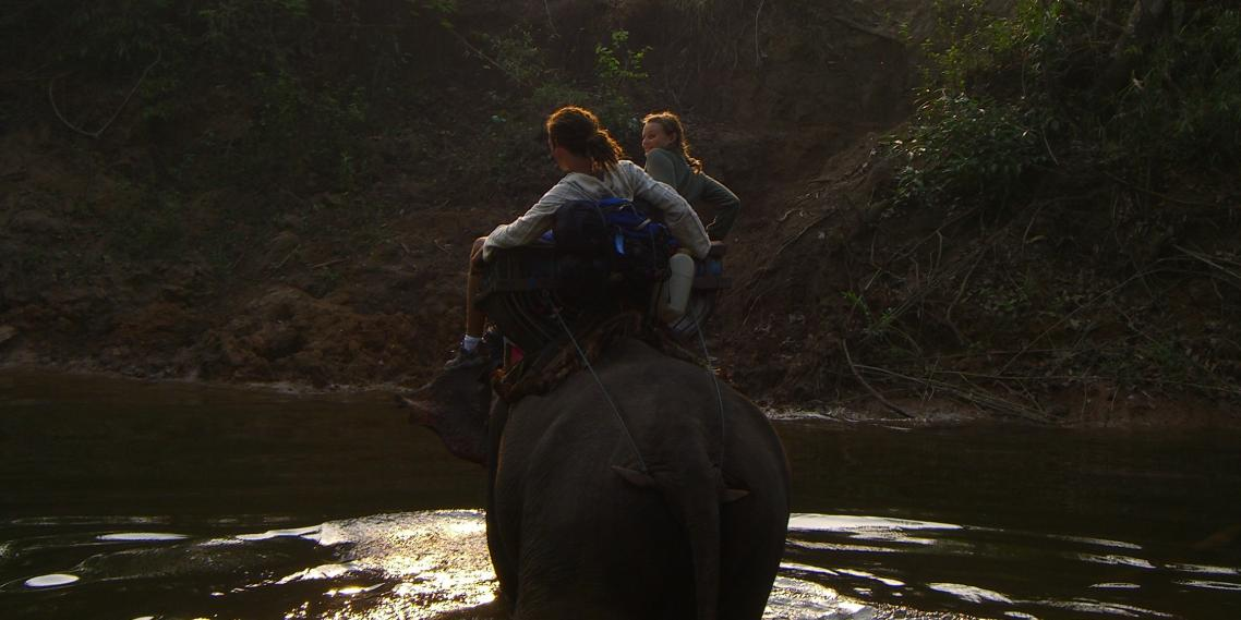 Tourists ride an elephant through a river in the jungle near Um Phang