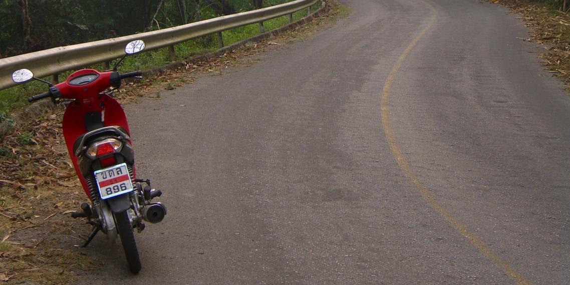 "A motorcycle sits on the ""easy,"" curving road up Doi Tung"