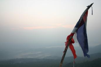 A Thai flag marks a mountain summit on a sunrise hike in Um Phang, Thailand
