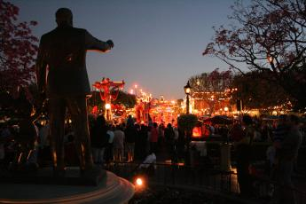 Disneyland at night as seen from behind the statue of Walt Disney and Mickey Mouse near Main Street