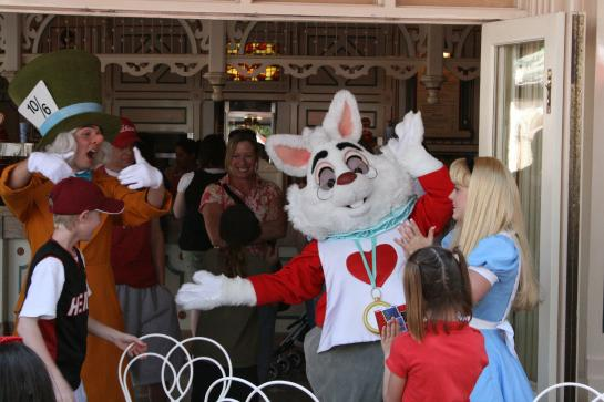 The Mad Hatter, White Rabbit, and Alice play Musical Chairs with children at Disneyland.