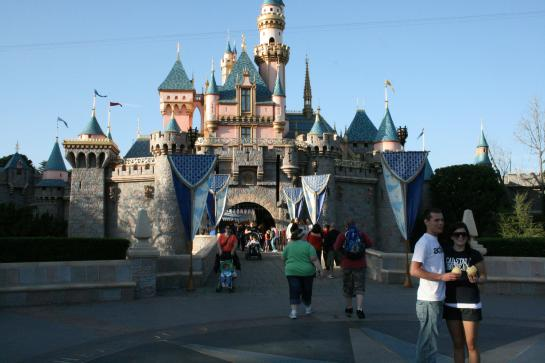 Couples enjoy posing for photos in front of Sleeping Beauty Castle in Disneyland.