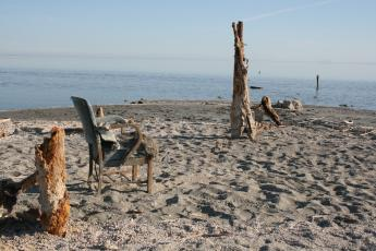 An abandoned chair sits on the shore of the Salton Sea