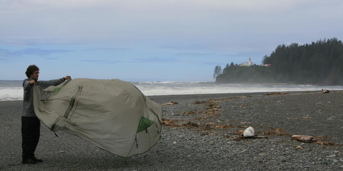 My brother Brian folds a wet tent in the morning after our hike's worst day