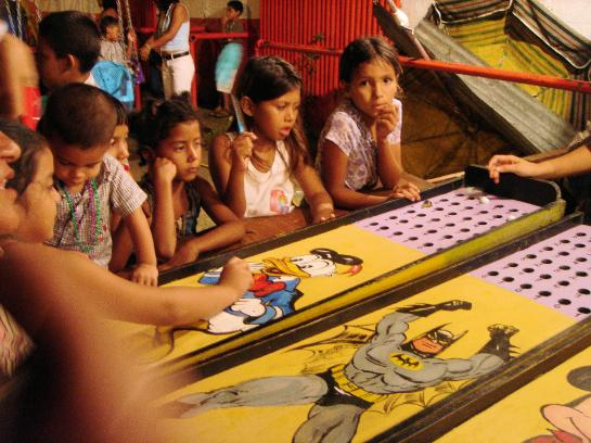 Children watch carnival games at a patron saint festival in Tela, Honduras.