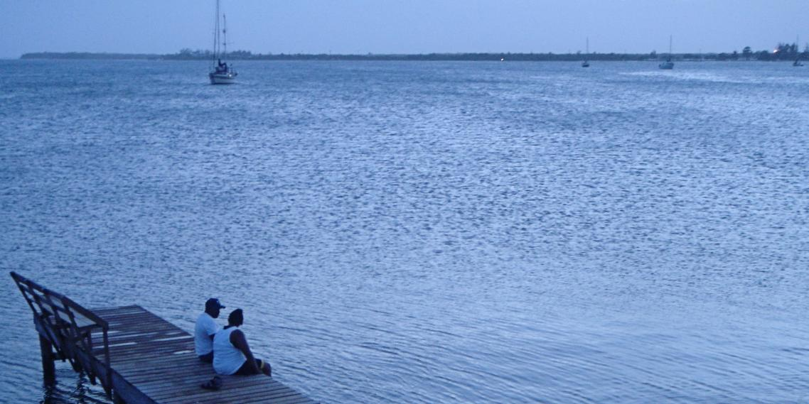 A couple looks at the horizon during magic hour in Utila, Honduras.