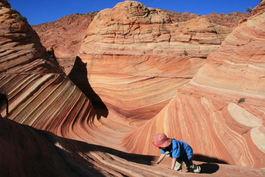 A child crawls on the red-orange sandstone at The Wave.