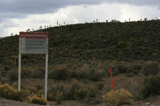 A sign warns trespassers at the boundary of Area 51 as security officers in a truck keep watch from a ridge.
