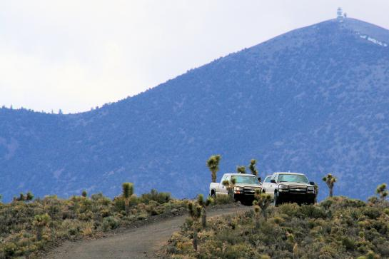 Area 51 security officers sit in trucks on a ridge watching for trespassers.