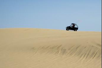 A traveler pilots a Yamaha Rhino across a sand dune in southern Oregon.