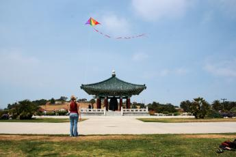 Suzy flies a kite in front of the  Korean Bell of Friendship.