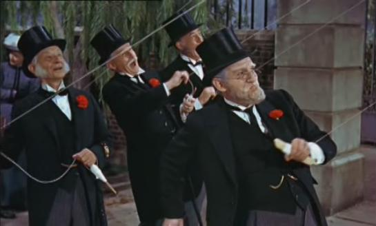 Formally-dressed bankers fly kites in Mary Poppins.