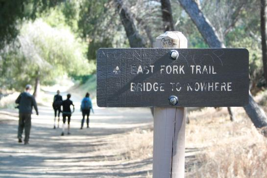 Hikers walk past the sign indicating the trail to the Bridge to Nowhere.