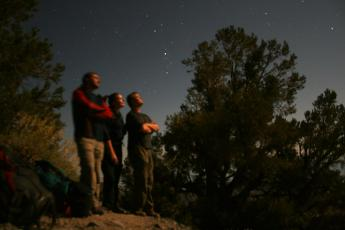 A 30-second exposure reveals hikers gazing at the moon near Death Valley's Telescope Peak.