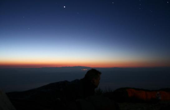 Rich watches the sunrise from his sleeping bag at the top of Death Valley's Telescope Peak.
