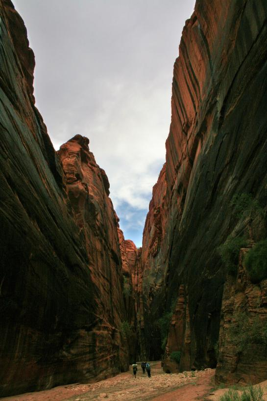 Hikers make their way through a particularly wide section of Buckskin Gulch.