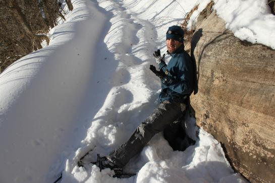 Brian reluctantly demonstrates the depth of the snow on the Grand Canyon's North Kaibab Trail.  Note that he is wearing snowshoes on both feet.