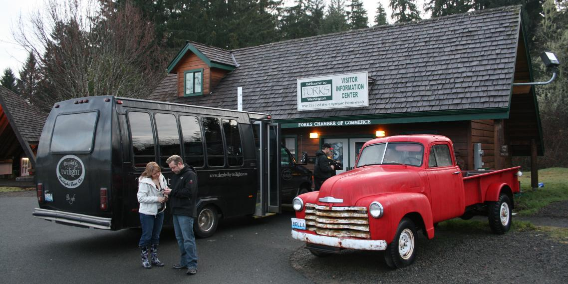 Twilight fans stand in front of the Forks Chamber of Commerce and a replica of Bella's 1953 Chevy pickup truck.