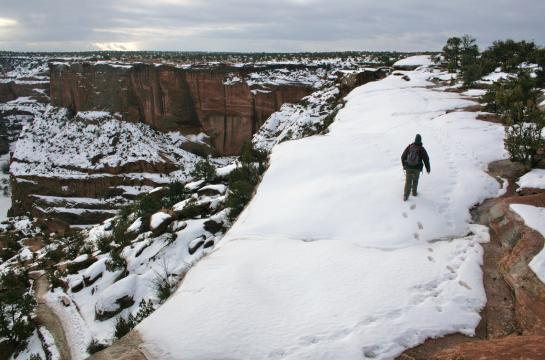 A hiker walks on a snowy ridge above Canyon de Chelly.