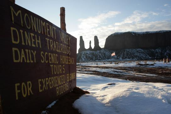 A sign advertises Monument Valley tours near the Three Fingers rock formation.