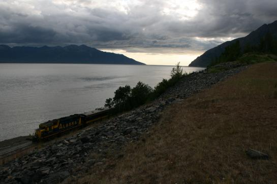 A train passes by the Cook Inlet in front of the Kenai Mountains near Alaska's Seward Highway.