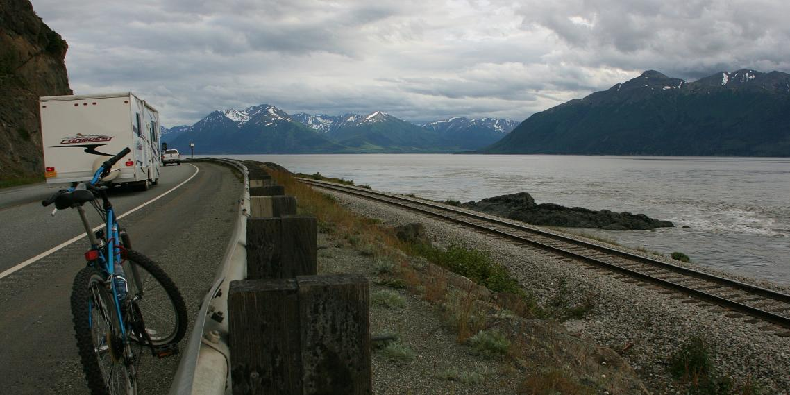 An RV passes a bicycle sitting on the Seward Highway near Alaska's Cook Inlet and Kenai Mountains.