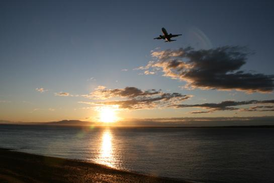 A plane flies over Point Woronzof as the sun sets near Anchorage's Coastal Trail.