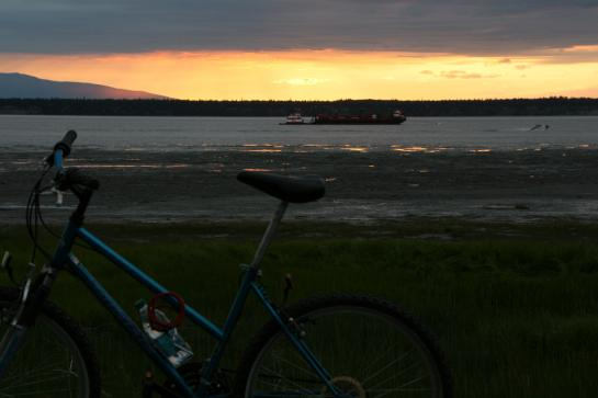 A bicycle sits on Anchorage's Coastal Trail as the sun sets over the Cook Inlet.