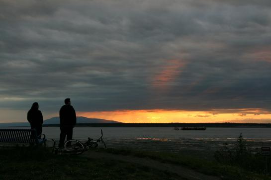 Cyclists watch the sunset from Anchorage's Coastal Trail.