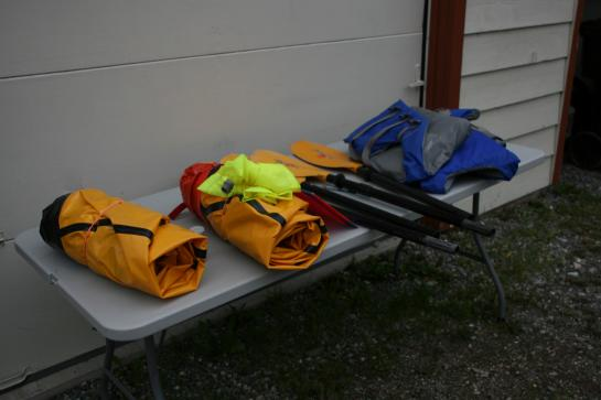 Packrafts, paddles, and life vests sit on a table ready to be packed.