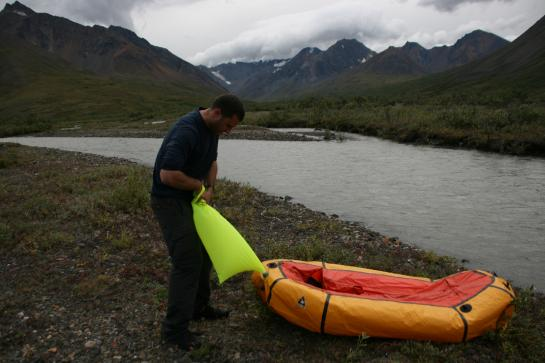 Hank inflates a packraft on the shore of Denali's Sanctuary River.