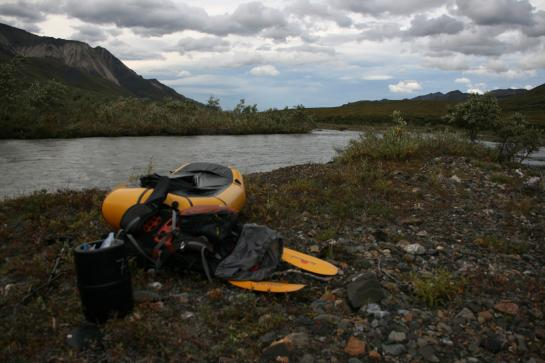 A packraft, a boat light enough to be carried in a backpack, sits on the edge of Sanctuary River in Denali National Park, Alaska.