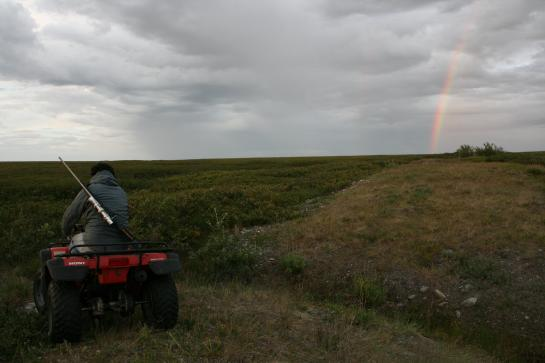 A rainbow appears in the arctic sky above an ATV.