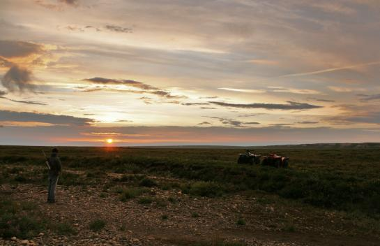 The sun dips toward the horizon above two ATVs.