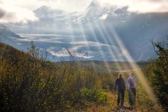 Hikers walk toward Portage Glacier in Whittier, Alaska.
