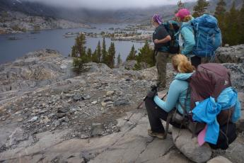 Hikers look out from John Muir Trail onto Garnet Lake in the Ansel Adams Wilderness in Northern California.