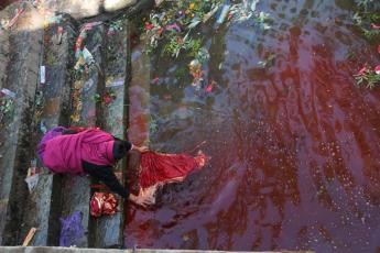 A woman soaks clothing in a blood-filled stream adjacent to the temple of Kali, Shiva's bloodthirsty consort.