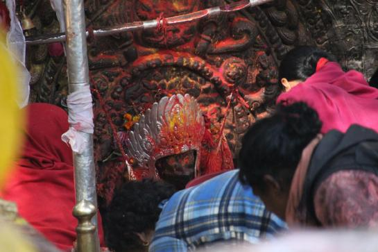 Nepalese worshippers bow before a blood-soaked statue of Kali. (photo by Brian Leukart)