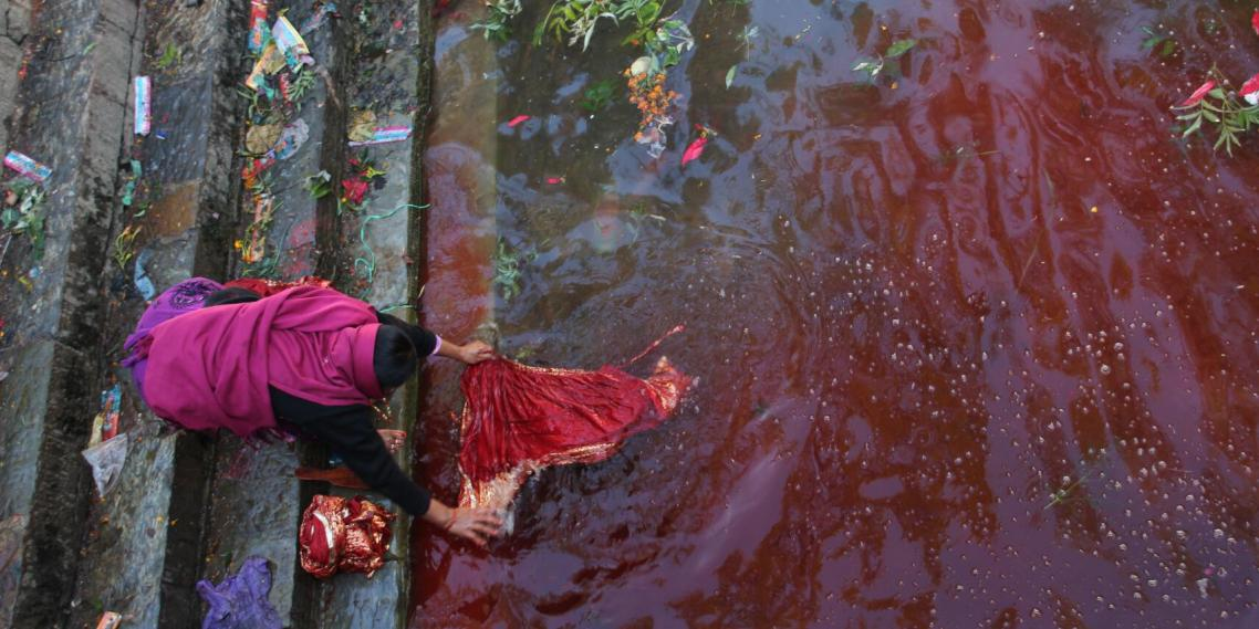 A woman soaks clothing in a blood-filled stream adjacent to the temple of Kali, Shiva's bloodthirsty consort. (photo by Brian Leukart)