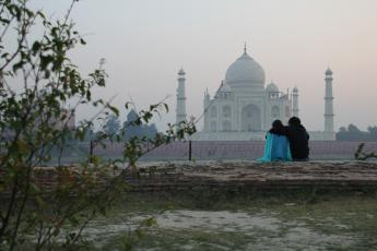 An Indian couple is entranced by the view of the Taj Mahal at sunset from Mehtab Bagh Park in Agra, India.