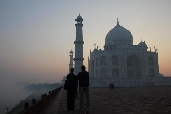 A couple gazes at the Taj Mahal from the bank of the Yamuna River.