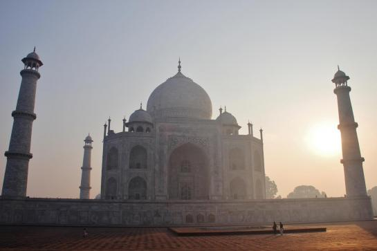 The sun rises behind the Taj Mahal.