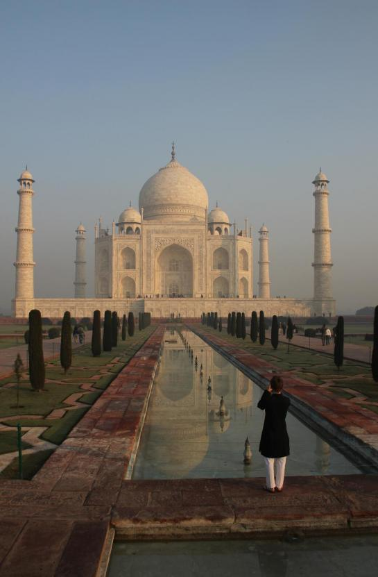 A woman photographs the Taj Mahal from the tip of the garden's reflection pool.