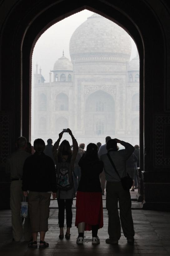 Tourists photograph the Taj Mahal through the complex's Great Gate at sunrise.
