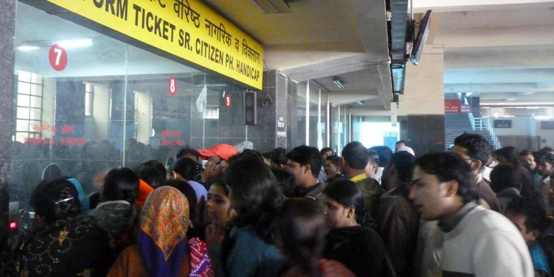 Customers clamor to buy tickets at the New Delhi train station.
