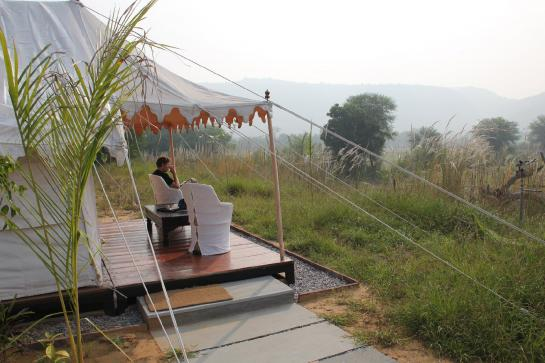 A tourist sits outside his luxury tent at Khem Villas near Ranthambore National Park, India.