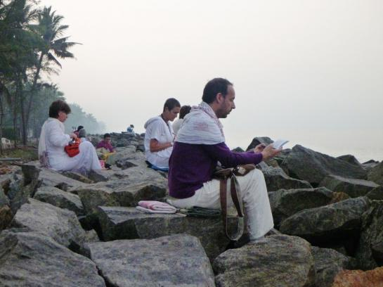 Devotees meditate on a beach in Amritapuri, India.