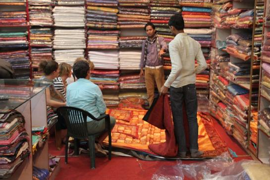 Tourists look at bed covers in a textiles shop in Jaipur, India.