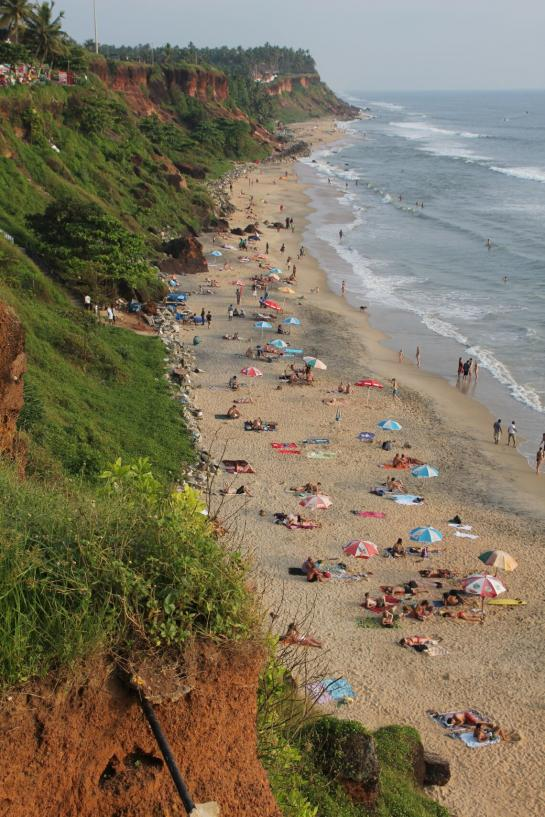 Tourists relax on the beach below cliffs in Varkala, India.