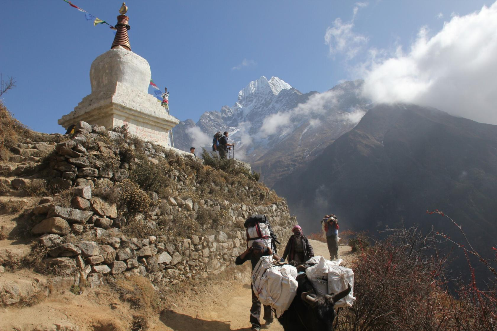 how to film yourself on a hiking trip to everest base camp hank looks out at the himalayan mountains next to a stupa near namche bazaar